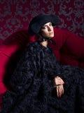 Klassisches Porträt der Frau das Endenkleid des schwarzen Hutes tragend, das auf rotem Sofa sitzt stockbild