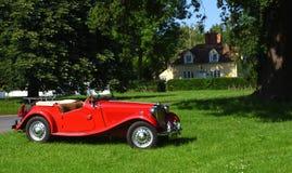 Klassisches rotes MG-Automobil geparkt auf Village Green Stockfotos