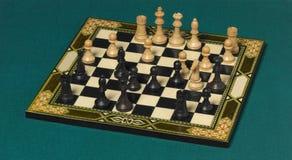 Klassisches Schachbrett mit Stücken über einem grünen Hintergrund Lizenzfreie Stockbilder