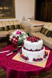 Klassisk bröllopstårta med hallon, jordgubbar, björnbär och blåbär royaltyfri bild