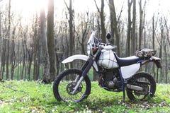 Klassisk enduromotorcykel av vägen i vårskogen, begrepp, aktiv livsstil royaltyfri bild