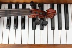 Klassisk fiol på träpianotangenter Klassisk fiol på pianot för musikbakgrundsbegrepp Defocused ljus av projektorer för gitarrillu royaltyfri bild