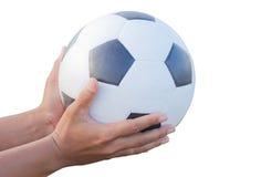 Klassisk fotbollboll i manliga händer. Arkivfoton