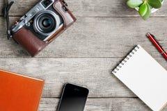 Klassisk kamera med den tomma notepadsidan och röd penna på den gråa trä, tappningtabellen med telefonen och den gröna blomman Br royaltyfri fotografi