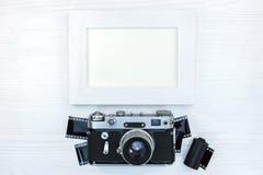 Klassisk kamera med negativa filmer och tom fotoram på whit Royaltyfria Foton