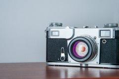 Klassisk kamera på hyllan på väggbakgrunden Royaltyfri Bild