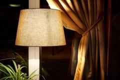 Klassisk lampa med dunkelt ljus nära fönster med den samlade gardinen royaltyfria bilder