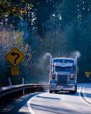 Klassisk mörk halv lastbil för stor rigg i solsken med att röka rör Arkivfoto