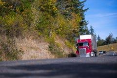 Klassisk modern röd halv lastbil torra skåpbil släp på höstvägen Royaltyfria Bilder