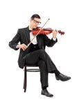 Klassisk musiker som spelar fiolen som placeras på stol Royaltyfri Foto