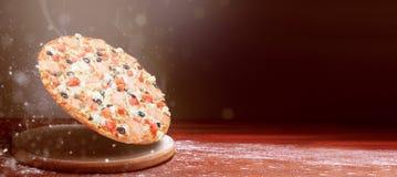 Klassisk pizza på en mörk trätabellbakgrund och en spridning av mjöl begrepp för pizzarestaurangmeny royaltyfri foto