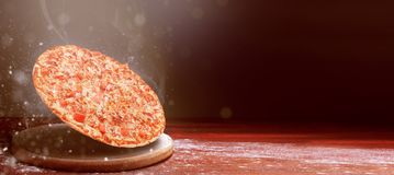 Klassisk pizza på en mörk trätabellbakgrund och en spridning av mjöl begrepp för pizzarestaurangmeny arkivfoto