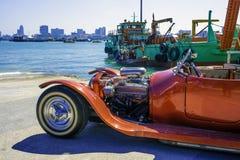 Klassisk röd bil som parkeras nära ett stort transportskepp på porten av Pattaya, Thailand royaltyfri bild