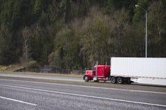 Klassisk röd halv lastbil för stor rigg med den halva släpet ru för kylskåp Royaltyfri Fotografi