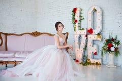 klassisk skönhet Härlig ung kvinna med stilfullt brunetthår och den eleganta klänningen som vilar i lyxig vit klassiker Royaltyfri Foto