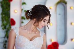 klassisk skönhet Härlig ung kvinna med stilfullt brunetthår och den eleganta klänningen som vilar i lyxig vit klassiker Arkivfoto