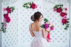 klassisk skönhet Härlig ung kvinna med stilfullt brunetthår och den eleganta klänningen som vilar i lyxig vit klassiker Arkivfoton