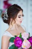 klassisk skönhet Härlig ung kvinna med stilfullt brunetthår och den eleganta klänningen som vilar i lyxig vit klassiker Arkivbild