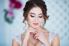 klassisk skönhet Härlig ung kvinna med stilfullt brunetthår och den eleganta klänningen som vilar i lyxig vit klassiker Royaltyfri Fotografi