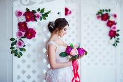 klassisk skönhet Härlig ung kvinna med stilfullt brunetthår och den eleganta klänningen som vilar i lyxig vit klassiker Fotografering för Bildbyråer