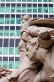 Klassisk skulptur och modern kontorsbyggnad Arkivfoto