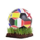 Klassisk soccerball med olika flaggor som ligger på ett stycke av gras som isoleras på vit bakgrund arkivbilder