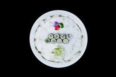 Klassisk sushirulle med gurkan på en vit rund platta som dekoreras med små blommor, japansk mat Top beskådar isolerat Royaltyfri Foto