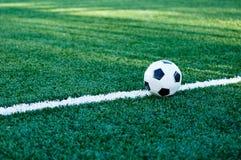 Klassisk svartvit fotbollboll på det gröna gräset av fältet royaltyfri bild