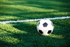 Klassisk svartvit fotbollboll på det gröna gräset av fältet Fotbolllek, utbildning, hobbybegrepp royaltyfria bilder