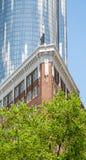 Klassisk tegelstenlägenhet och modernt blått Glass torn Royaltyfria Bilder