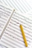 Klassisk träblyertspenna med skriftlig musik Fotografering för Bildbyråer