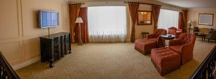 Klassisk vardagsrum med soffan, fåtöljer, tabeller, TVuppsättningen och l Arkivfoto