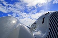 Klassisk vit sportbil med moln och himmel royaltyfri bild