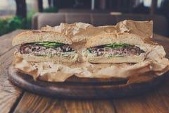 Klassiska amerikanska hamburgare, snabbmat på wood bakgrund Arkivbild