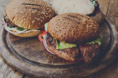 Klassiska amerikanska hamburgare, snabbmat på wood bakgrund Royaltyfria Foton