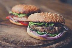 Klassiska amerikanska hamburgare, snabbmat på wood bakgrund Arkivfoton
