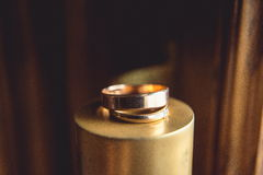 Klassiska guld- vigselringar på överkanten av den guld- kotten Arkivfoton