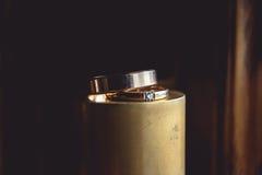 Klassiska guld- vigselringar på överkanten av den guld- kotten Arkivbild