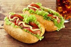 Klassiska hotdogs med drinken av cola på träbräde Royaltyfri Foto