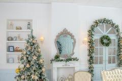Klassiska lägenheter med en vit spis, ett dekorerat granträd, en soffa, en spegel, stora dörrar med fönster och en ljuskrona arkivfoton