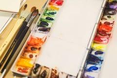 Klassiska naturliga borstar för att dra med vattenfärger och en palett med olika målarfärger som är förberedda för att dra royaltyfria foton