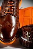 Klassiska polerade mäns brogues med apelsinen sular och bryner bältet Royaltyfria Bilder