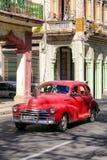 Klassiska röda Chevrolet i gammal havannacigarr på en färgrik gata royaltyfri fotografi