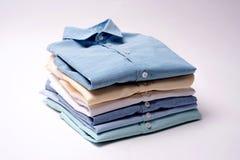 Klassiska skjortor för man` som s staplas på vit bakgrund royaltyfri foto