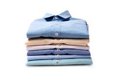 Klassiska skjortor för man` som s staplas på vit bakgrund arkivfoton