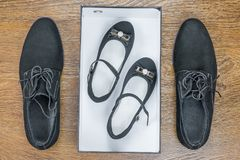 Klassiska skor för man` s på golvet och behandla som ett barn i en ask arkivbilder