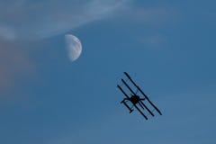 Klassiskt flygplanflyg mot månen på en blå himmel i solnedgången arkivfoton