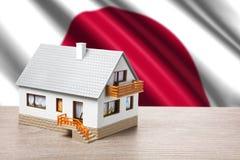 Klassiskt hus på japansk flaggabakgrund arkivfoto