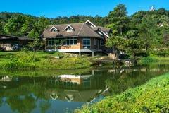 Klassiskt lyxigt hus med vattenreflexion, den gröna trädgården och kanalen i Pilok gammalt bryta i denläderrem byn, Pilok, läderr arkivbild