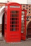 Klassiskt rött engelskt telefonbås på gatan, öppen dörr, inga personer royaltyfria foton